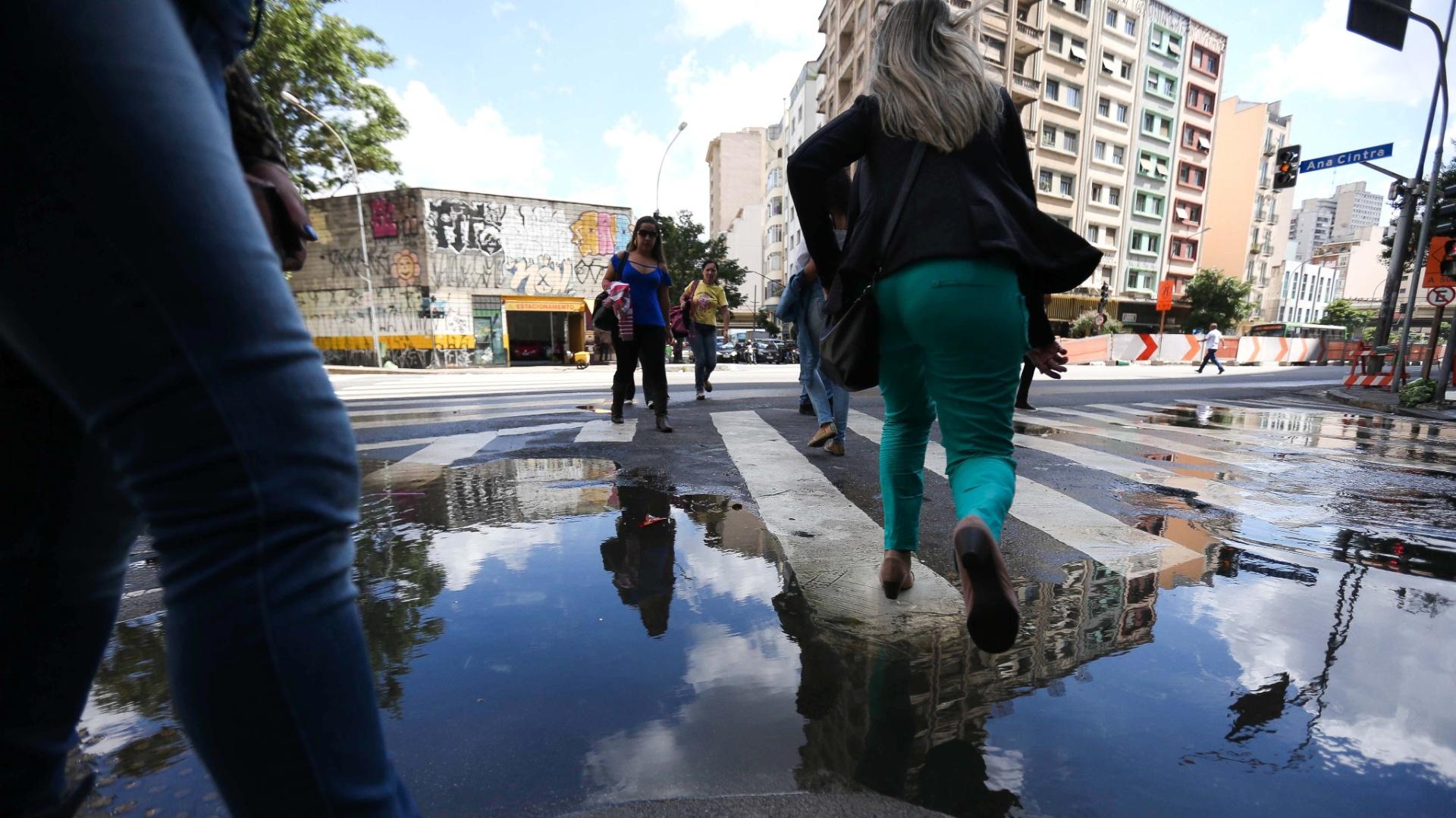 26.mar.2015 - Mulher pula uma poça de água acumulada na esquina entre a rua Ana Cintra e a avenida São João, no centro de São Paulo, nesta quinta-feira (26). A água vem de uma tubulação em frente ao imóvel número 1.474 da avenida São João