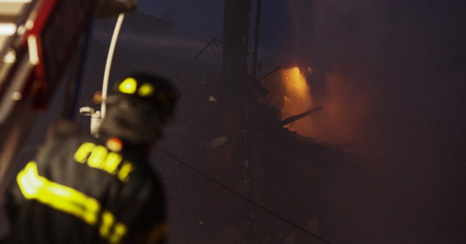 26.mar.2015 - Policiais fazem patrulha enquanto bombeiros trabalham para controlar o incêndio que tomou um edifício na Segunda Avenida, no East Village, em Nova York (EUA), nesta quinta-feira (26). O incêndio foi causado por uma explosão e, logo depois que as chamas se espalharam, uma parte da construção desabou. Várias pessoas ficaram feridas, algumas em estado grave, segundo informações locais