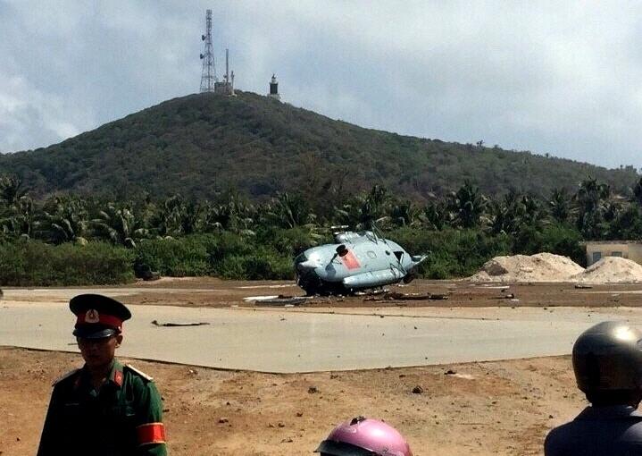 26.mar.2015 - Policiais observam o local de um acidente com um helicóptero militar na ilha de Phu Quy, região central do Vietnã. Ao menos três soldados vietnamitas foram feridos nesta quinta quando o aparelho caiu sobre a pista de pouso a cerca de 1.100 km da capital Hanói