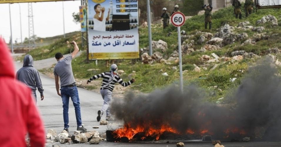 27.mar.2015 - Palestinos atiram pedras em soldados do Exército israelense durante um protesto contra o assentamento judaico de Bel El, ilegal sob a lei internacional, no campo de refugiados em Yalazón, na Cisjordânia