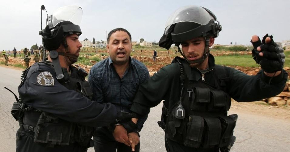 28.mar.2015 - Manifestante palestino é preso pelas forças de segurança israelenses durante confrontos após um protesto contra a expansão das colônias judaicas na Cisjordânia