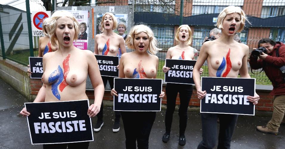 29.mar.2015 - Ativistas do grupo Femen protestam diante do local de votação da líder francesa do partido de extrema direita Frente Nacional, em Henin-Beaumont, no norte da França, neste domingo (29). O país vai às urnas para o segundo turno das eleições regionais. Os cartazes em francês dizem: