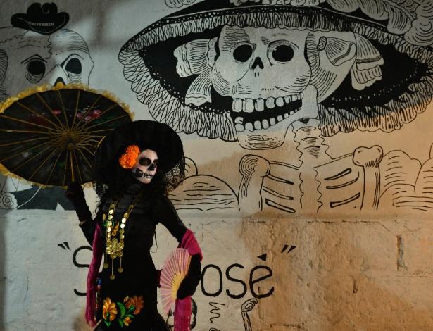 """30.mar.2015 - Mulher vestida de """"La Catrina"""", a grande dama da morte mexicana, posa em frente a um mural com a personagem durante a comemoração do Dia dos Mortos, em San José Etia, no Estado de Oaxaca, México"""