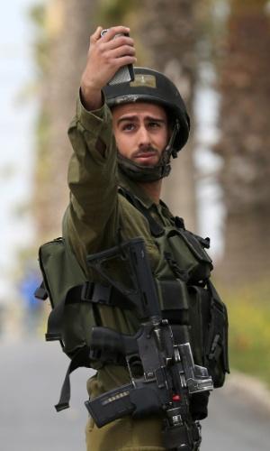30.mar.2015 - Soldado israelense faz selfie durante confronto com manifestantes palestinos após protesto marcando o Dia da Terra, nesta segunda-feira (30), no vilarejo de Silwad, norte de Ramallah, na Cisjordânia. As manifestações foram realizadas para lembrar os seis manifestantes árabe-israelenses que foram mortos a tiros pela polícia e tropas israelenses durante manifestações em massa em 1976, contra os planos de confiscar terras árabes na Galileia