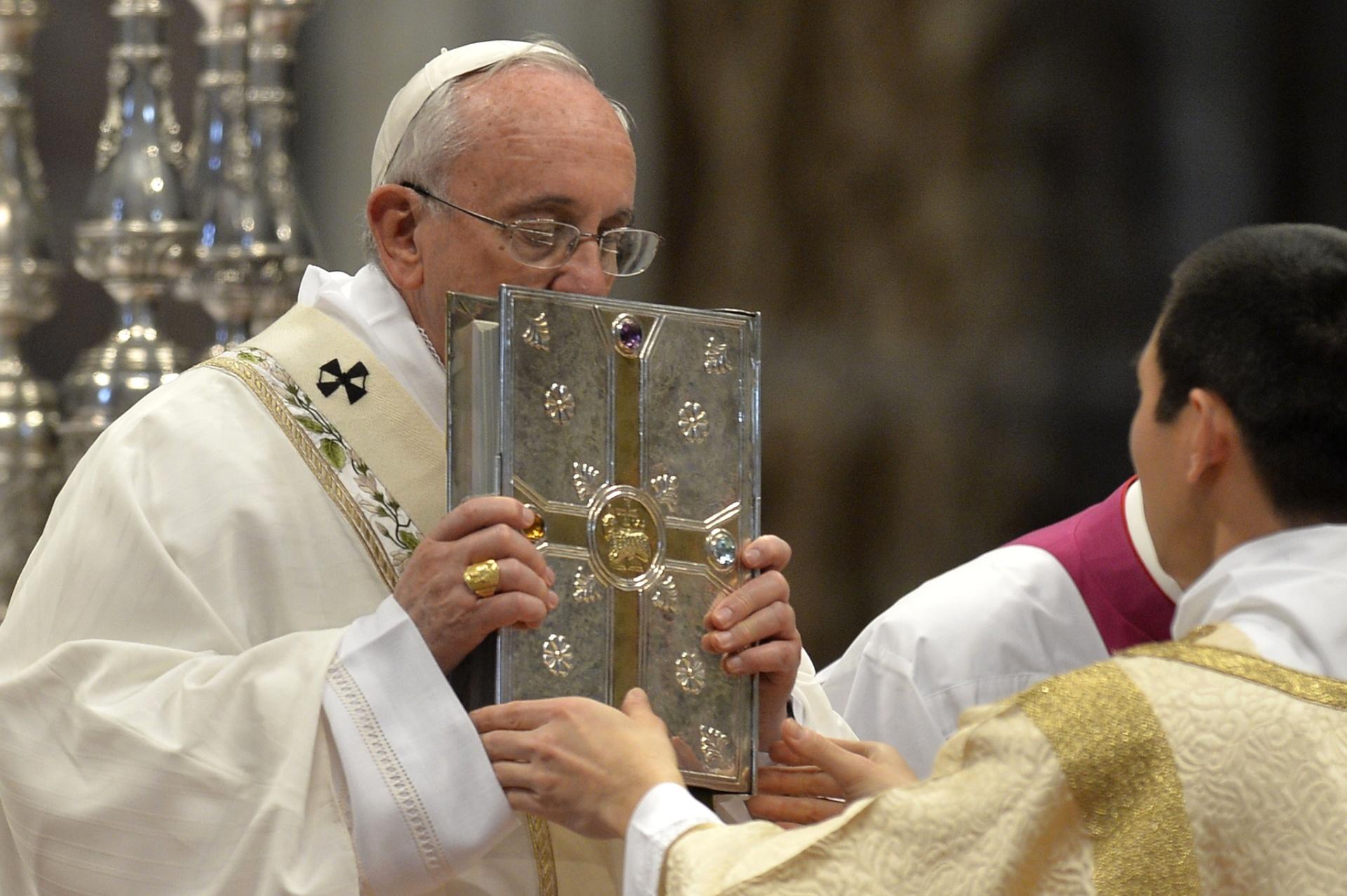 2.abr.2015 - O papa Francisco beija a bíblia durante missa de celebração da quinta-feira santa, dia que marca o início das comemorações da Páscoa, nesta quinta-feira (2), na Basílica de São Pedro, no Vaticano