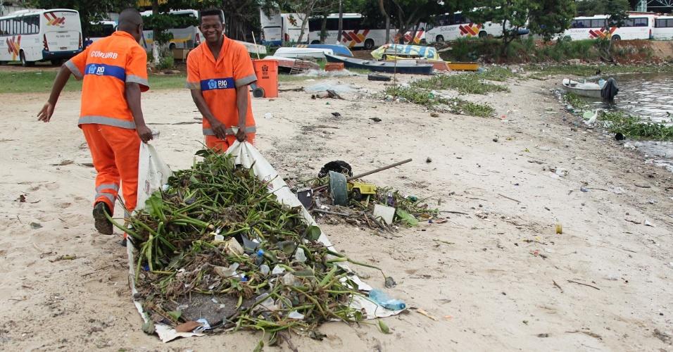 2.abr.2015 - Funcionários da limpeza recolhem parte de lixo da praia da Rosa, na baía de Guanabara, na zona oeste da cidade do Rio de Janeiro