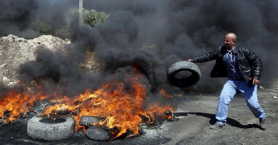 3.abr.2015 - Manifestante palestino joga um pneu em uma fogueira durante confrontos com soldados israelenses, após um protesto contra a colonização judaica na aldeia de Kofr Qadom, na Cisjordânia