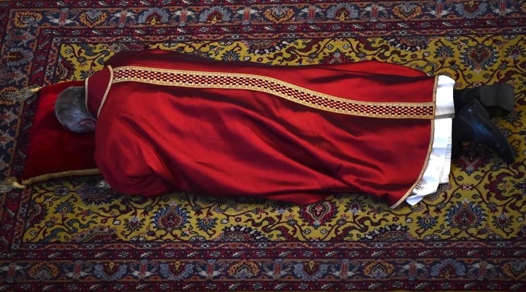 3.abr.2015 - Papa Francisco deita de bruços no chão da basílica de São Padro, no Vaticano, durante a missa da Sexta-Feira Santa