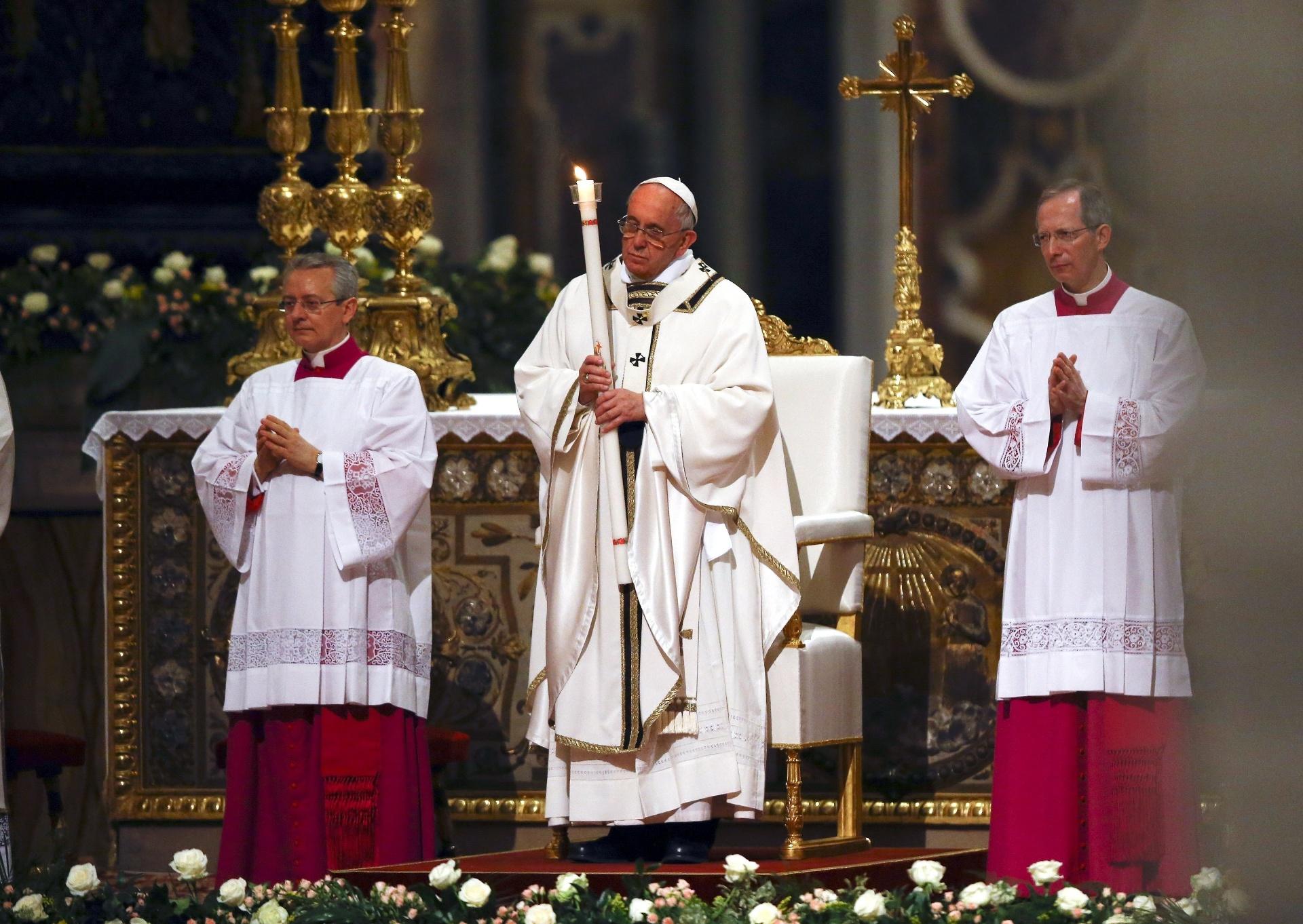 4.abr.2015 - O papa Francisco segura uma vela ao chegar para missa de Páscoa na Basília de São Pedro, no Vaticano
