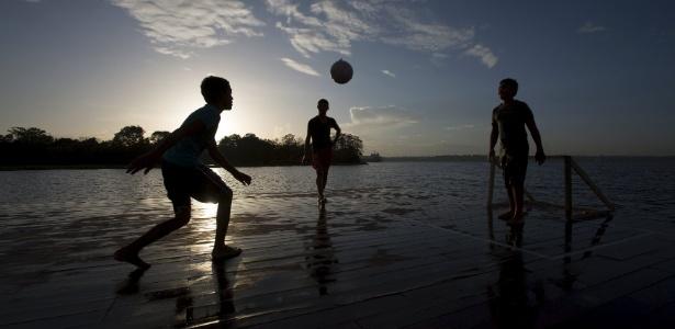 Garotos jogam futebol em plataforma sobre o rio Negro, perto de Manaus