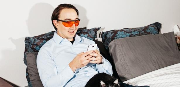 Matt Nicoletti checa telefone com óculos laranja, em sua casa em Denver, EUA - Benjamin Rasmussen/The New York Times