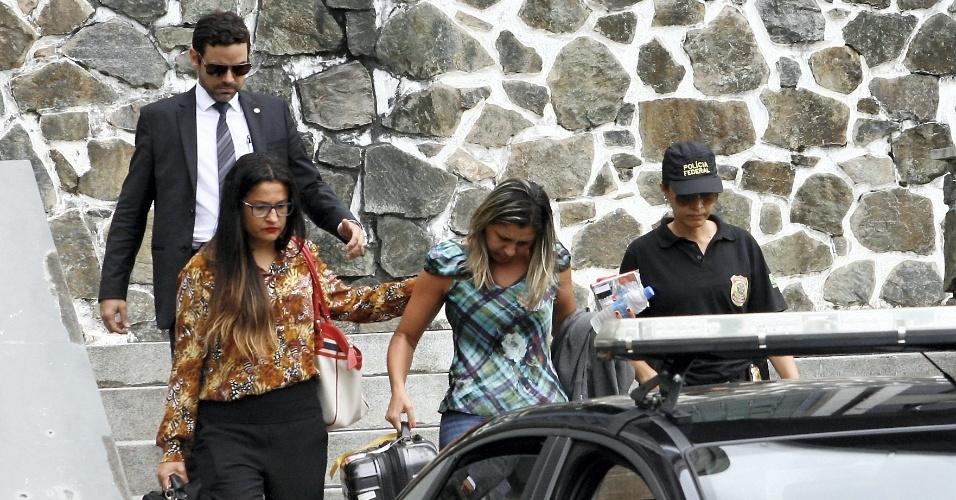 10.abr.2015 - A secretária do ex-deputado Luiz Argôlo (SD- BA), Élia Santos da Hora, acompanhada por sua advogada Cristiane Costa(à esq.) e policiais federais, é conduzida até o veículo que a levará até o Aeroporto de Salvador, de onde embarca com destino a Curitiba (PR). A Polícia Federal prendeu hoje três ex-deputados em uma nova etapa da operação Lava Jato. Ao todo, cerca de 80 Policiais Federais cumprem 32 mandados judiciais: sete mandados de prisão, nove mandados de condução coercitiva e 16 mandados de busca e apreensão nos Estados do Paraná, Bahia, Ceará, Distrito Federal, Pernambuco, Rio de Janeiro e São Paulo