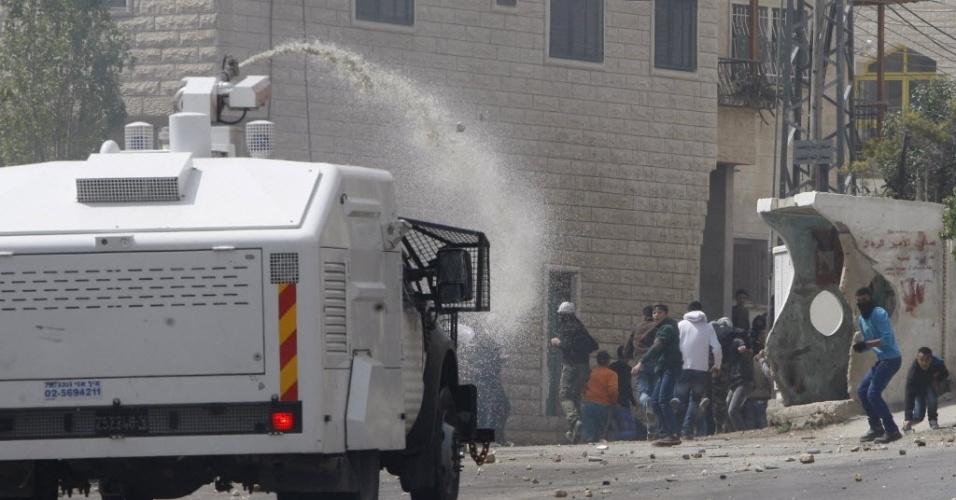 10.abr.2015 - Policiais israelenses usam canhões de água contra palestinos durante confrontos em Beit Omar, perto da cidade de Hebron. Um palestino morreu e cerca de 20 ficaram feridos nesta sexta-feira ao serem atingidos por disparos das forças de segurança israelenses quando participavam de um funeral em uma cidade próxima a Hebron, no território ocupado da Cisjordânia