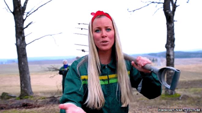 """Cercadas de fardos de feno, vestindo macacões verdes, dirigindo tratores, alimentando vacas e comendo hambúrgueres, jovens universitárias da Noruega cantam uma música de defesa aos agricultores e contra a reforma no setor proposta pelo governo. O vídeo, """"A Noruega Precisa do Fazendeiro"""", já foi visto mais de 163 mil vezes no You Tube. Em uma cena, o grupo persegue uma personagem que se parece com a ministra da Agricultura do país, Sylvi Listhaug. """"Várias gerações cuidaram da fazenda, mas as reformas do governo destruir as normas. Poderíamos ter um novo governo no país, por favor?"""", dizem - Reprodução/BBC Brasil"""