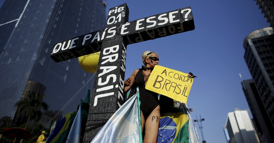 """12.abr.2015 - Manifestante segura um cartaz apoiada em uma cruz onde se pode ler """"Que país é esse?"""" durante protesto contra o governo da presidente Dilma Roussef, na avenida Paulista, centro de São Paulo, neste domingo (12)"""