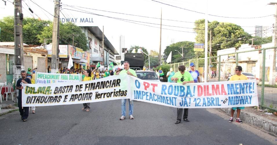 """12.abr.2015 - Manifestantes carregam cartaz em que se lê """"Basta de financiar ditaduras e apoiar terroristas"""" durante protesto pelo impeachment da presidente Dilma Rousseff em Natal, Rio Grande do Norte. A concentração da passeata aconteceu em frente ao Midway Mall"""