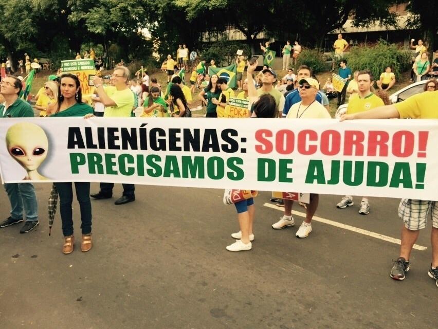 12.abr.2015 - Manifestantes seguram uma faixa pedindo ajuda aos alienígenas durante protesto contra o governo da presidente Dilma Rousseff em Porto Alegre (RS). A imagem foi enviada pelo internauta Marina Costa para o WhatsApp do UOL - (11) 97500 1925