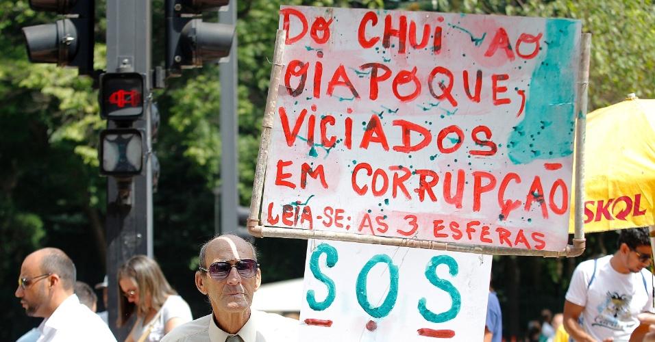 """12.abr.2015 - Manifestante segura cartaz com a frase """"Do Chuí ao Oiapoque viciados em corrupção"""" durante protesto contra o governo da presidente Dilma Rousseff na avenida Paulista, em São Paulo"""