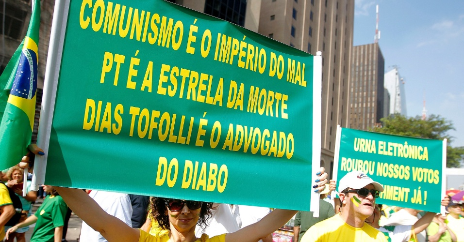 """12.abr.2015 - Manifestante ergue cartaz com os dizeres """"Comunismo é o império do mal, PT é a estrela da morte"""" durante protesto contra o governo da presidente Dilma Rousseff na avenida Paulista, em São Paulo"""