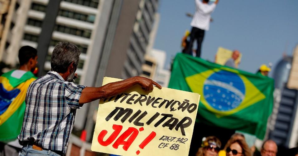 """12.abr.2015 - Manifestante segura cartaz com os dizeres """"Intervenção militar já!"""" durante protesto contra o governo da presidente Dilma Rousseff na avenida Paulista, em São Paulo"""