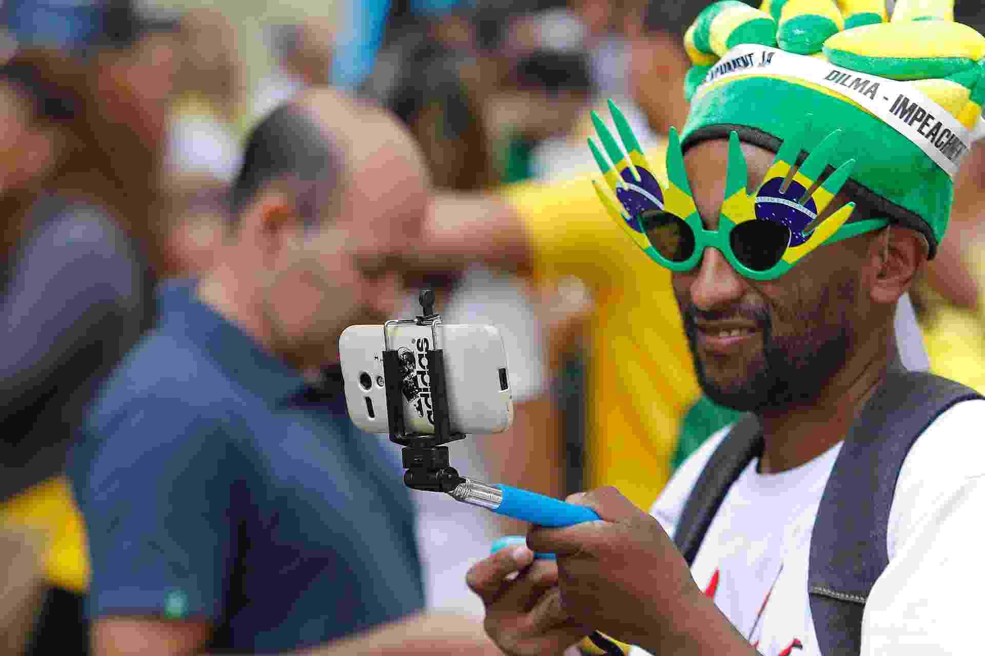 12.abr.2015 - Manifestante usa 'pau de selfie' durante protesto contra o governo da presidente Dilma Rousseff na avenida Paulista, em São Paulo - Reinaldo Canato/UOL