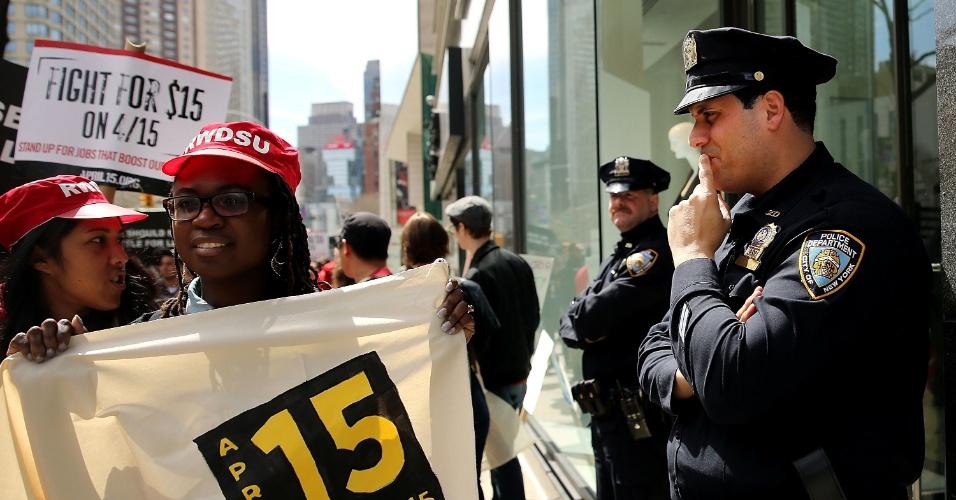 15.abr.2015 - Policiais de Nova York observam manifestantes em protesto contra práticas trabalhistas em redes de fast food nos EUA