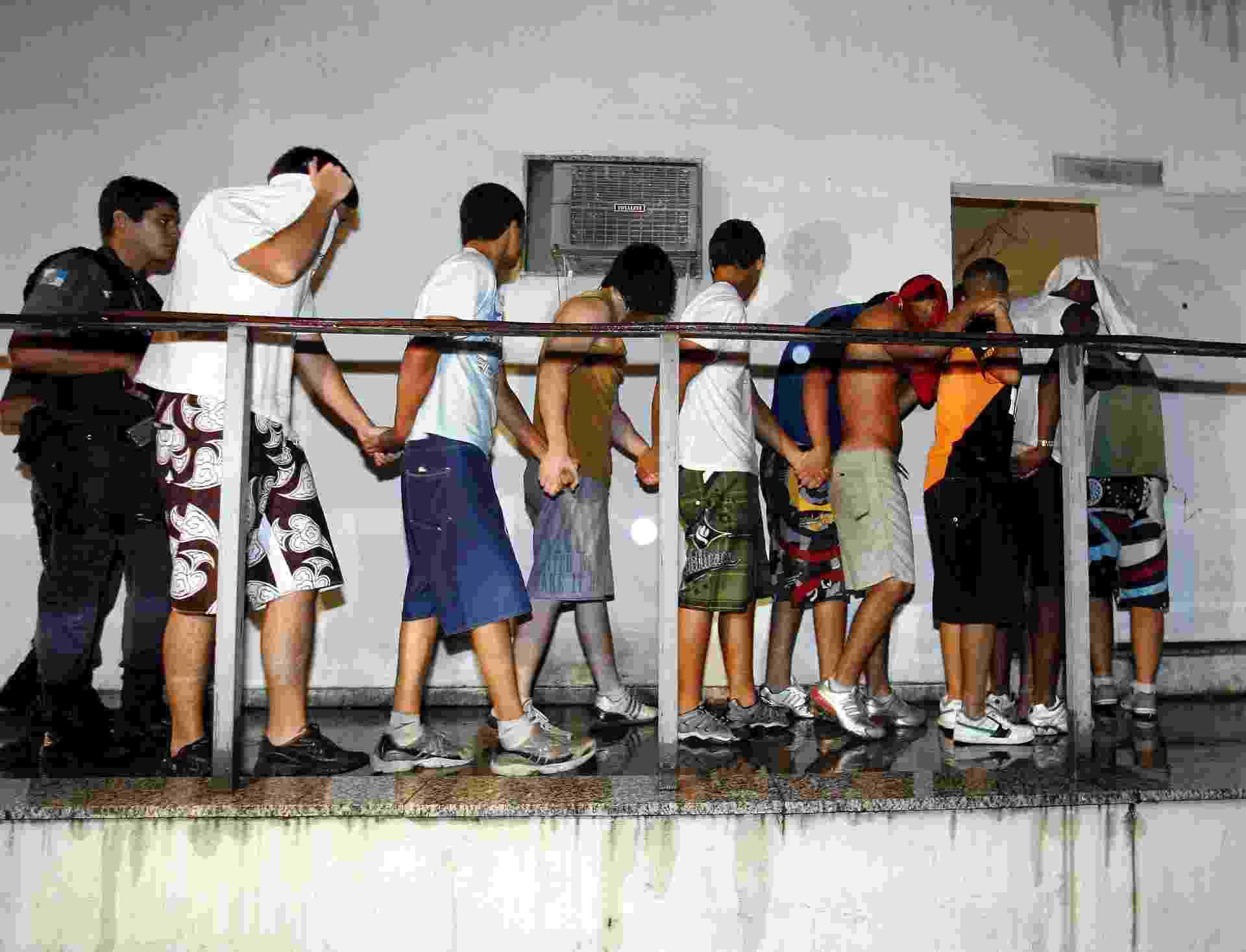 15.abr.2015 - Policial conduz jovens detidos após briga na zona norte do Rio de Janeiro (RJ) - Celso Meira/Agência O Globo