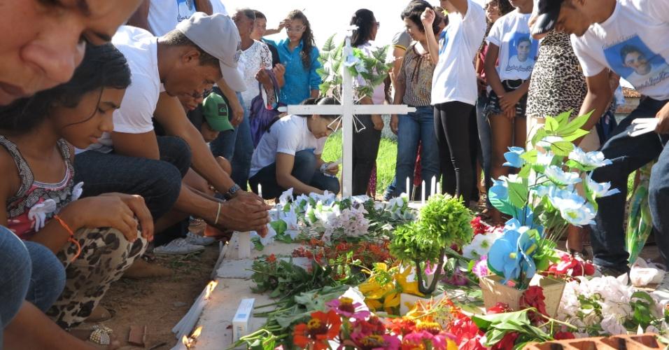 12.abr.2015 - Amigos e familiares cobriram o túmulo de cimento, sem lápide nem inscrições, com flores de plástico e velas