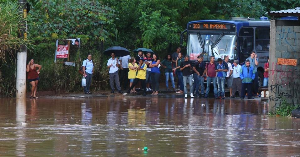 16.abr.2015 - Ônibus e moradores do bairro Rochdale em Osasco (SP) ficam sem passagem com rua alagada após forte chuva nesta quinta-feira (16)