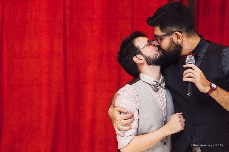 """Os noivos Thomas e Juca se beijam durante o casamento deles em 22 de março de 2014. O álbum da cerimônia foi eleito o melhor do ano na edição de 2015 do prêmio Wedding Best, que premia as melhores fotos de casamentos do Brasil. As fotos são do fotógrafo Rafael Karelisky. É a primeira vez que um álbum que retrata uma união homoafetiva vence o prêmio. Para Karelisky, bicampeão do Wedding Best, é """"coisa de outro mundo ser vencedor outra vez"""" e """"muito importante"""" por ter sido com fotos de uma união gay"""