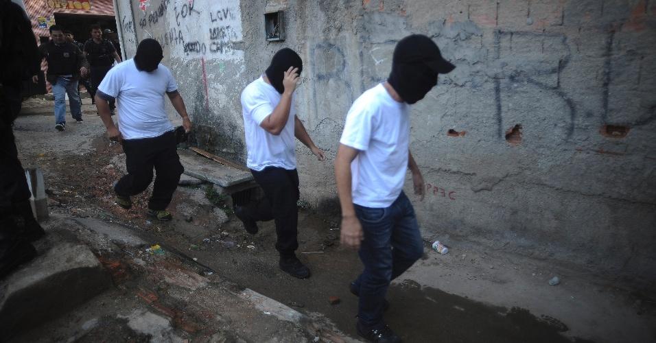 17.abr.2015 - Policiais militares chegam encapuzados ao Complexo do Alemão, na zona norte do Rio de Janeiro, para participar da reconstituição da morte do menino Eduardo de Jesus Ferreira, 10, nesta sexta-feira