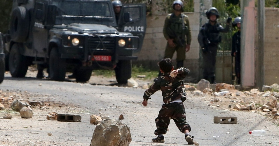 17.abr.2015 - Uma criança palestina joga uma pedra contra forças israelenses durante confronto entre manifestantes palestinos e forças de segurança após uma manifestação em apoio a homens palestinos detidos em prisões israelenses e contra a expropriação de terras por Israel, nesta sexta-feira (17), no vilarejo de Kfar Qaddum, próximo a Nablus, na Cisjordânia