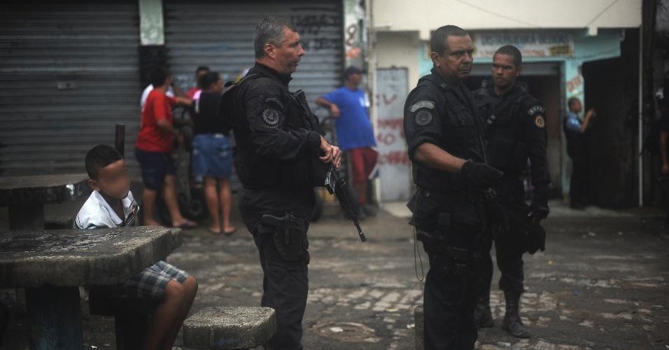 9.abr.2015 - Criança observa o trabalho de policiais no Complexo do Alemão, na zona norte do Rio de Janeiro. No dia 2 de abril, o menino Eduardo de Jesus Ferreira, 10, foi morto por um tiro de fuzil na porta de casa durante uma ação da Polícia Militar. A foto foi tirada na quinta-feira (9)