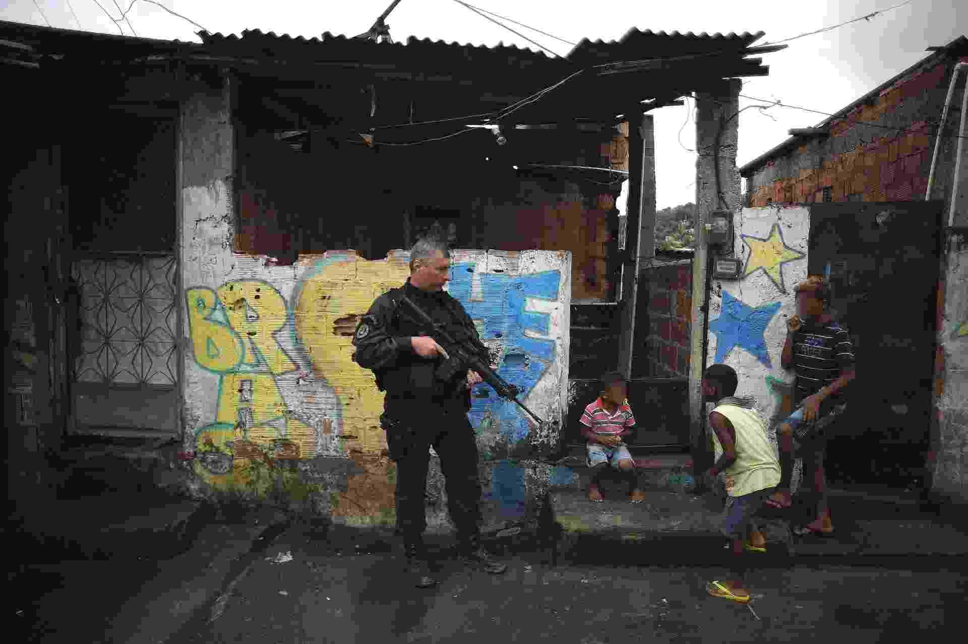 9.abr.2015 - Crianças brincam perto de policiais em rua no Complexo do Alemão, na zona norte do Rio de Janeiro. No dia 2 de abril, o menino Eduardo de Jesus Ferreira, 10, foi morto por um tiro de fuzil na porta de casa durante uma ação da Polícia Militar. A foto foi feita na quinta-feira (9) - Fábio Teixeira/UOL