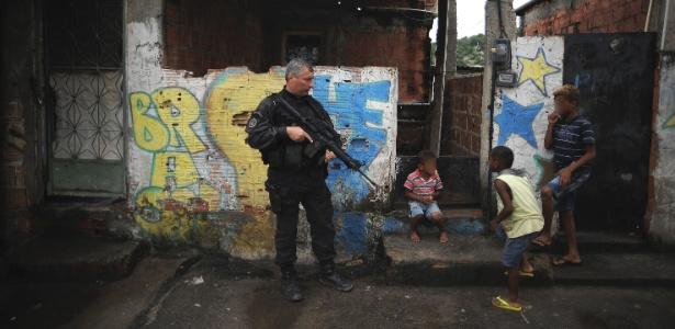 9.abr.2015 - Crianças brincam perto de policiais em rua no Complexo do Alemão, na zona norte do Rio de Janeiro