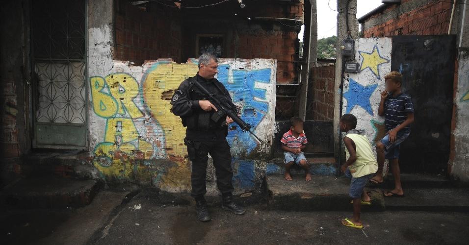9.abr.2015 - Crianças brincam perto de policiais em rua no Complexo do Alemão, na zona norte do Rio de Janeiro. No dia 2 de abril, o menino Eduardo de Jesus Ferreira, 10, foi morto por um tiro de fuzil na porta de casa durante uma ação da Polícia Militar. A foto foi feita na quinta-feira (9)