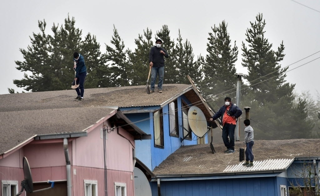 23.abr.2015 - Moradores retiram cinzas vulcânicas do telhado da casa onde moram em La Ensenada, no Chile. O vulcão Calbuco entrou em erupção na quarta-feira (22), expelindo um funil gigante de cinzas