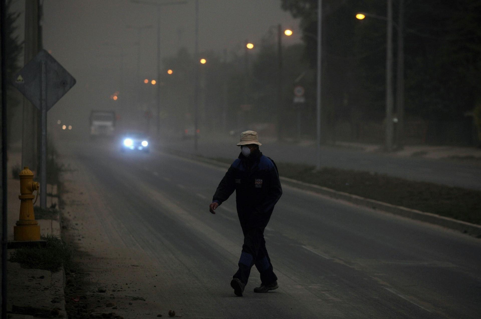 23.abr.2015 - Um homem usa uma máscara enquanto caminha ao meio dia por uma rua de Pucón, coberta por cinzas expelidas pelo vulcão Calbudo, a 400 km ao norte de Puerto Varas, no Chile, nesta quinta-feira (23). O vulcão entrou em erupção na quarta-feira (22) pela primeira vez em quase meio século e está entre os três mais perigosos dos 90 vulcões ativos no país. O alerta vermelho (máximo) está em vigor nas cidades de Puerto Montt e Puerto Varas, situadas na região de Los Lagos, cerca de 1.300 km ao sul de Santiago. As aulas estão suspensas na região e os voos foram proibidos sobre a zona em alerta