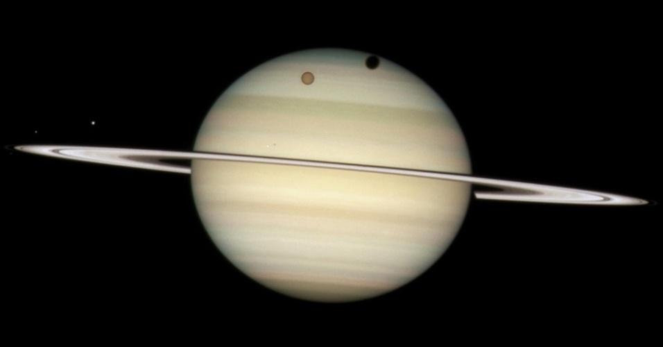 24.abr.2015 - Em 24 de fevereiro de 2009, quando os anéis de Saturno estavam bastante finos e planos, o Hubble localizou quatro das luas de Saturno enquanto elas passavam pela face do planeta. Nesta imagem, a lua alaranjada Titã faz uma sombra redonda e profunda na borda superior do disco de Saturno.