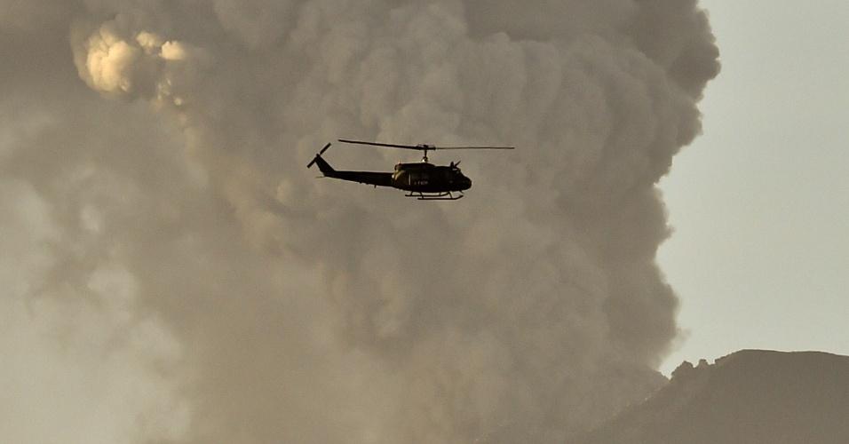 24.abr.2015 - Helicóptero passa perto das cinzas expelidas pelo vulcão Cabulco, em Puerto Varas, no Chile, nesta sexta-feira (24). O sul do país permaneceu em alerta sexta-feira para outra erupção do vulcão