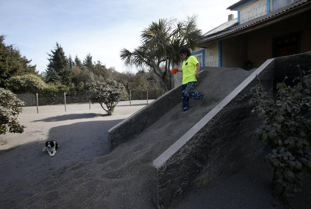 24.abr.2015 - Moradora tenta descer as escadas de sua casa cobertas por cinzas expelidas pelo vulcão Cabulco, em Ensenada, na região dos Lagos, no sul do Chile, nesta sexta-feira (24). O vulcão entrou em erupção na última quarta-feira (22) e continua instável, expulsando fumaças e cinzas, por isso que não se pode descartar que haja uma nova explosão, disseram as autoridades nesta sexta-feira (24)