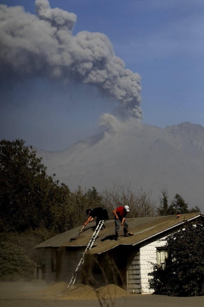 24.abr.2015 - Moradores tiram cinzas do telhado de um casa após a erupção do vulcão Cabulco, em El Arrayán, no sul do Chile, nesta sexta-feira (24). O vulcão entrou em erupção na última quarta-feira (22) e continua instável, expulsando fumaças e cinzas. Especialistas afirmam que não se pode descartar uma nova explosão