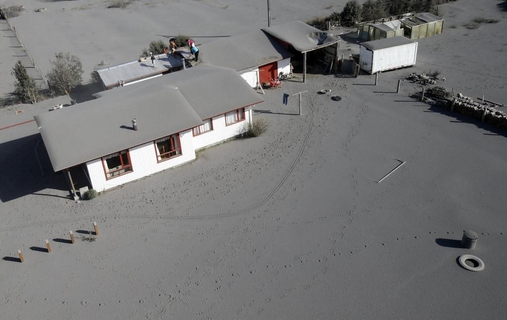 24.abr.2015 - Moradores tiram de seus telhados as cinzas expelidas pelo vulcão Calbuco em Ensenada, na região dos Lagos, no sul do Chile, nesta sexta-feira (24). O vulcão entrou em erupção na última quarta-feira (22) e continua instável, expulsando fumaças e cinzas, por isso que não se pode descartar que haja uma nova explosão, disseram as autoridades nesta sexta-feira (24)