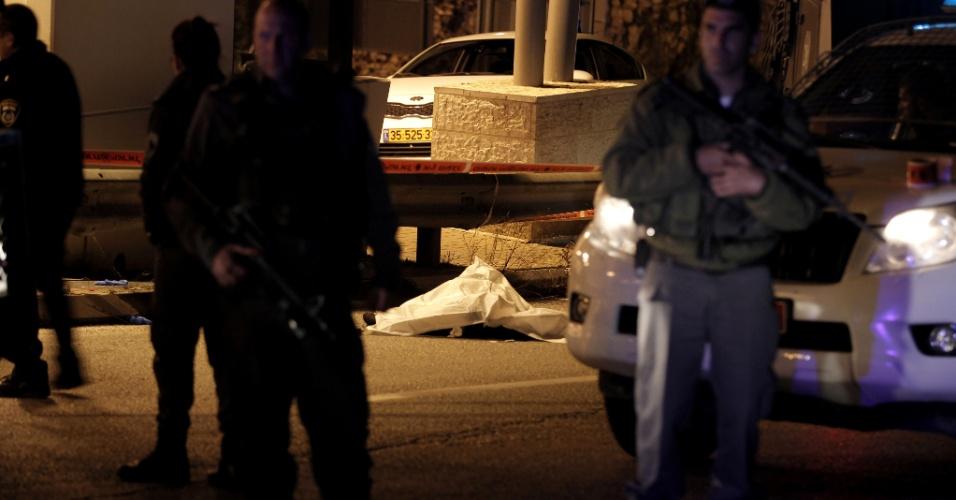 25.abr.2015 - As tropas israelenses montam guarda ao lado do corpo coberto de um palestino de 17 anos de idade mortos a tiros por soldados perto do posto de controle de Al-Zaim, nos arredores de Jerusalém Oriental - parte ocupada da Cisjordânia por Israel-, neste sábado (25). Segundo porta-voz de Israel, o jovem foi morto após tentar esfaquear um policial