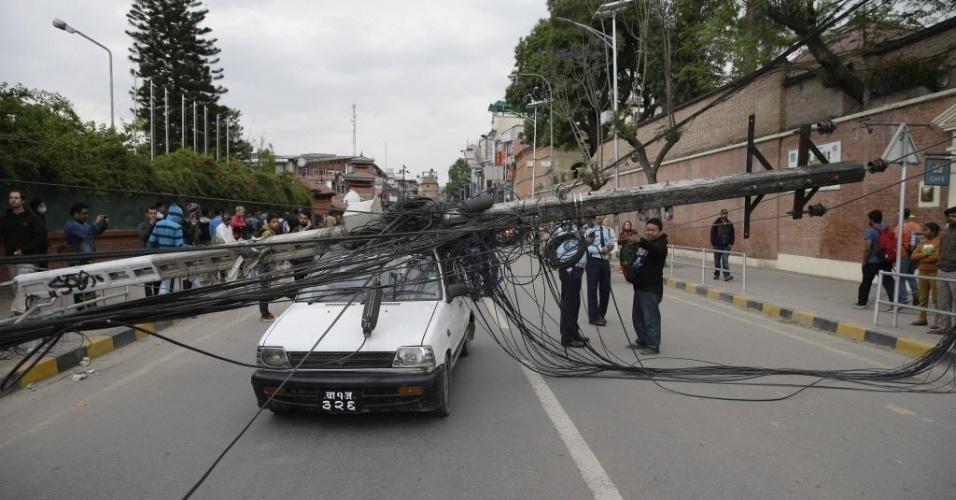 25.abr.2015 - Carro é atingido por poste da rede de energia elétrica em Katmandu (Nepal), durante o forte terremoto que atingiu a cidade neste sábado (25). O número de mortos chega a centenas, de acordo com informações divulgadas pelo Ministério do Interior. Com magnitude 7,8, os tremores causaram o colapso de vários prédios e construções históricas no Nepal, e também foram sentidos na Índia, Paquistão e Bangladesh