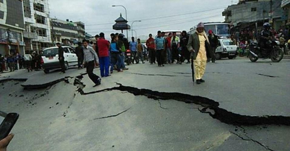 25.abr.2015 - Uma rachadura corta o asfalto nesta rua de Katmandu, onde centenas de pessoas morreram após a ocorrência de tremores de alta intensidade. Com medo dos desabamentos, a população saiu para as ruas
