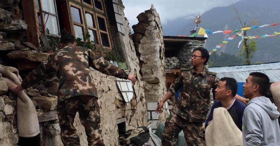 25.abr.2015 - Soldados chineses ajudar moradores em Gyirong, no Tibete, a retirar pertences de casa danificada pelo terremoto de 7,8 com epicentro no Nepal, ocorrido neste sábado. Ao menos 17 pessoas morreram e 13 ficaram na província chinesa do Tibete, enquanto mais de 1.800 pessoas morreram no Nepal, e mais de 4.000 ficaram feridas