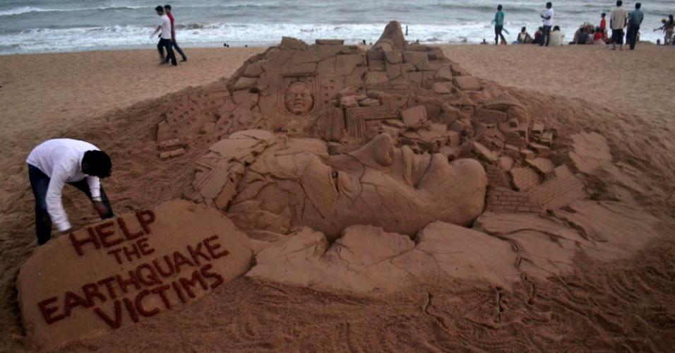 26.abr.2015 - Artista indiano cria escultura em uma praia de Puri, na Índia, para pedir ajuda às vítimas do terremoto que devastou o Nepal