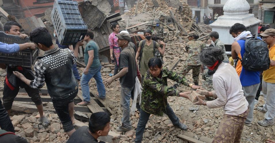 26.abr.2015 - Mediante a falta de infraestrutura e mão-de-obra especializada, civis auxiliam nas buscas por sobreviventes em meios aos escombros da Praça Durbar, em Kathmandu, um dia após o pior abalo sísmico do Nepal desde 1934. Os voluntários retiram os concretos com as próprias mãos