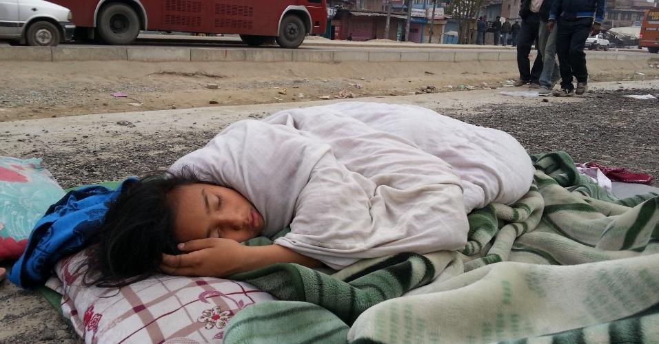 26.abr.2015 - Menina dorme em uma rua de Katmandu, no Nepal, em meio as suspeitas de novos tremores no país que foi devastado por terremoto de magnitude 7.8. Foi o pior abalo sísmico do país desde 1934